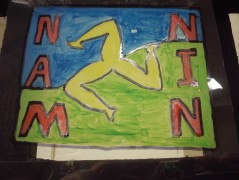 """Painting of a yellow symbol with a green and blue background. Red letters spell """"NAM NIN"""""""
