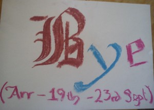 "The word ""Bye"" is written in gothic font. The B is brown, the y is blue and the e is black. Underneath, in pink lettering, it says ""(Arr - 19th - 23rd Sept)"