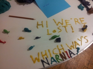 "Photograph of playdough snails. The words ""Hi we're lost! Which way is Narnia?"" are spelled out in letters made of playdough."