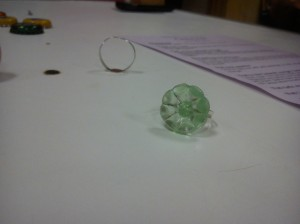 Photo of a green plastic flower on a white table
