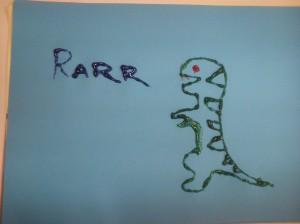 Green dinosaur drawn on white paper with glitter glue