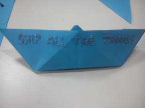 """Blue paper boat with the words """"Ship all the things"""" written in silver"""