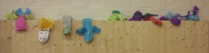 Photograph of 9 sock puppets on a wooden ledge