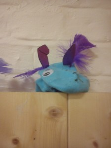 A blue sock puppet with long purple ears and purple feathers