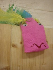 A pink sock puppet with yellow feathers