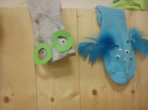 A blue sock puppet with multiple eyes and blue feathers and a grey sock puppet with green glasses made of card