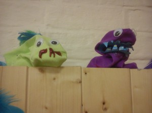 A pale green sock puppet with red glitter glue moustache, and a purple sock puppet with blue teeth.